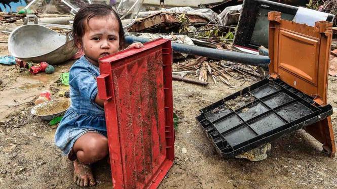 Seorang bocah bermain dengan barang yang rusak diterjang gelombang tsunami Selat Sunda di Kecamatan Sumur, Pandeglang, Banten