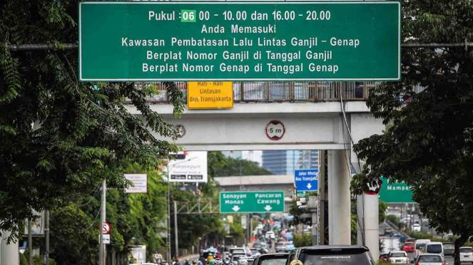 Kendaraan melintasi papan informasi penerapan sistem ganjil genap di Jakarta.