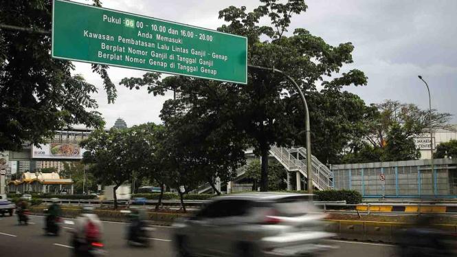 Kendaraan melintasi papan informasi penerapan sistem ganjil genap di Jalan Jenderal Gatot Subroto, Semanggi, Jakarta