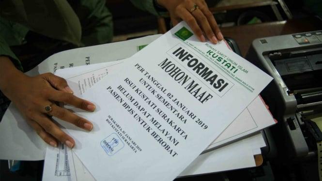 Petugas menunjukkan lembar informasi penghentian sementara pelayanan untuk pasien Badan Penyelenggara Jaminan Sosial (BPJS) karena masalah akreditasi di Rumah Sakit Umum Islam (RSUI) Kustati Solo, Jawa Tengah