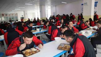 Para peserta didik kamp pendidikan vokasi etnis Uighur di Kota Kashgar, Daerah Otonomi Xinjiang, Cina, makan siang bersama dengan menu halal, di kantin, saat jam istirahat, Jumat, 3 Januari 2019.