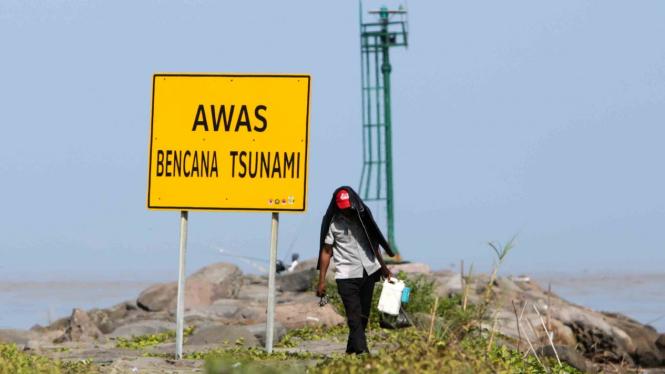 Warga berjalan di dekat rambu peringatan bencana tsunami.