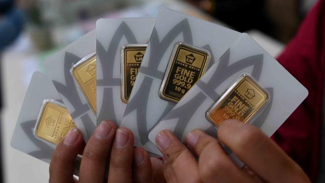 Konsumen menunjukkan emas batangan yang dibelinya di Butik Emas Logam Mulia, Gedung Aneka Tambang, Jakarta