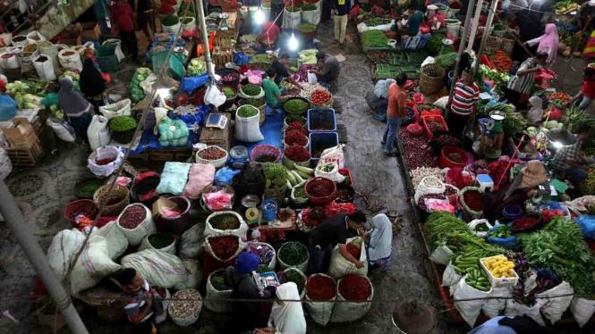 Aktivitas pedagang dan konsumen di pasar tradisional sayur dan rempah-rempah.