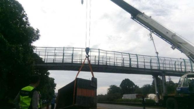 Badan truk tersangkut di JPO Tol Jakarta-Merak dievakuasi.