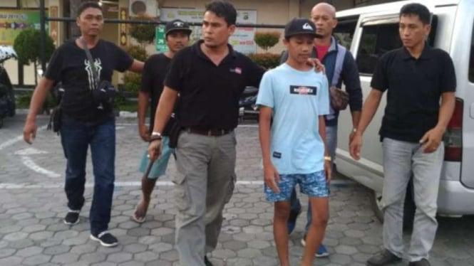 Pelaku saat digiring polisi menuju Markas Polres Mataram.