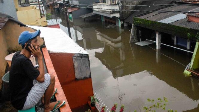 Warga menelepon di atas rumahnya saat banjir di Kecamatan Manggala, Makassar, Sulawesi Selatan.