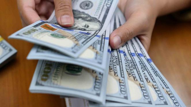 Karyawan menghitung mata uang dolar Amerika Serikat di gerai penukaran mata uang asing Ayu Masagung, Kwitang, Jakarta Pusat