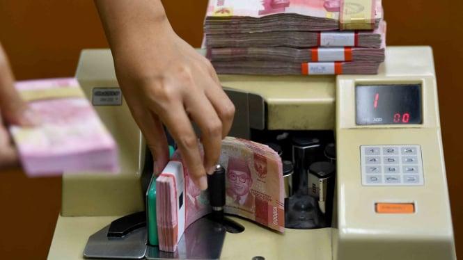 Karyawan menghitung mata uang rupiah Indonesia di gerai penukaran mata uang asing Ayu Masagung, Kwitang, Jakarta Pusat