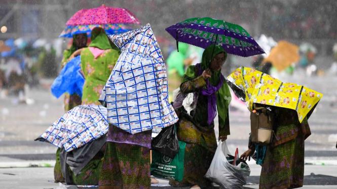Peserta mengenakan payung akibat hujan ketika mengikuti rangkaian Harlah ke-73 Muslimat Nahdlatul Ulama (NU), doa bersama untuk keselamatan bangsa dan maulidrrasul di Stadion Utama Gelora Bung Karno, Jakarta