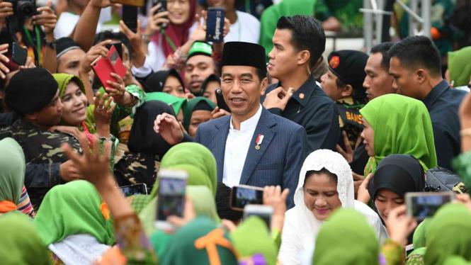 Presiden Joko Widodo (tengah) didampingi Ketua Muslimat Nahdlatul Ulama (NU) Khofifah Indar Parawansa (kedua kanan) menghadiri Harlah ke-73 Muslimat NU, doa bersama untuk keselamatan bangsa dan maulidrrasul di Stadion Utama Gelora Bung Karno, Jakarta