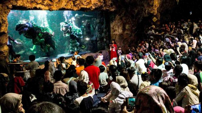 Pengunjung menyaksikan pertunjukan barongsai di dalam air di Seaworld Ancol, Jakarta, Minggu, 3 Februari 2019.