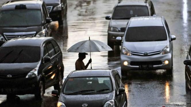 Warga menyeberang menggunakan payung saat hujan di Jakarta
