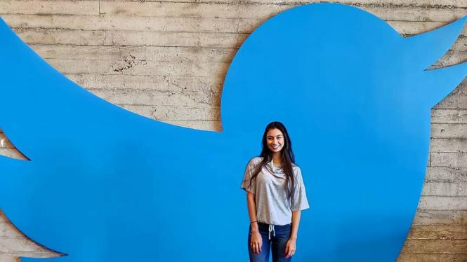 Seorang pengunjung berpose di depan logo Twitter.