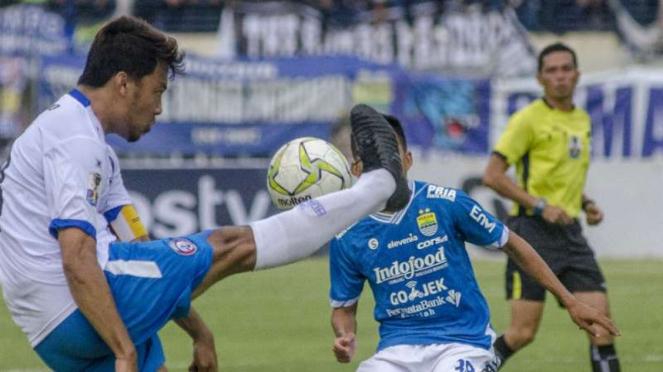 Bek Arema FC, Hamka Hamzah (kiri) saat melawan Persib Bandung.