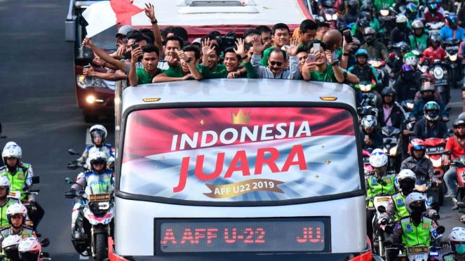 Pemain dan ofisial Timnas U-22 Indonesia menaiki bus tingkat ketika mengikuti konvoi menuju Istana Negara saat melintas di Jalan Sudirman, Jakarta, Kamis, 28 Februari 2019.
