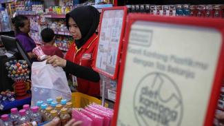 Pramuniaga memasukkan barang yang telah dibeli konsumen ke dalam kantong plastik di salah satu mini market di kawasan Jakarta Timur, Jumat, 1 Maret 2019.