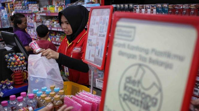 Pramuniaga memasukkan barang yang telah dibeli konsumen ke dalam kantong plastik di salah satu mini market. (ilustrasi)