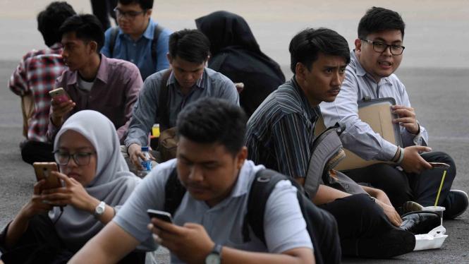 """Para pencari kerja beristirahat disela-sela acara Indonesia Spectacular Job Fair """"JOB FOR CAREER"""" Festival 2019 di kawasan Stadion Utama Gelora Bung Karno, Jakarta"""