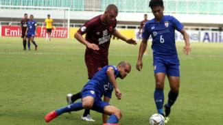 Gelandang PSM Makassar, Willem Jan Pluim, saat berebut bola dengan pemain Lao
