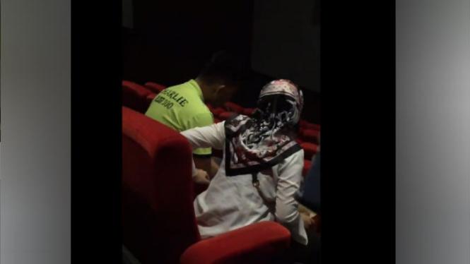 Pria merokok di bioskop.