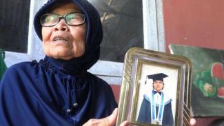 Yusni (71) ibu dari Zulfirman Syah tengah memperlihatkan foto korban.