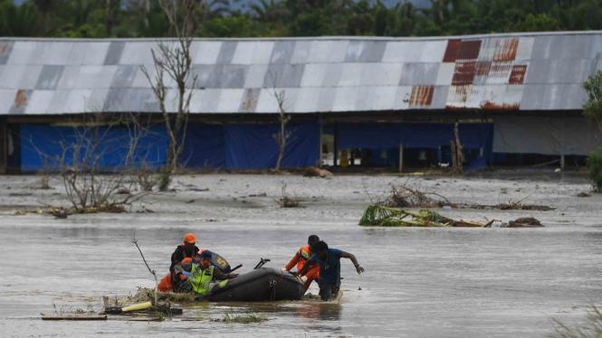 Tim SAR Gabungan mendorong perahu karet yang memuat  jenazah korban banjir bandang Sentani yang di temukan di sekitar perumahan Gajah Mada di  Sentani, Jaya Pura, Papua, Selasa, 19 Maret 2019.