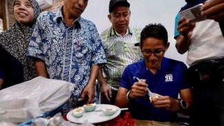 Cawapres Sandiaga Uno saat mencicipi telur asin bersama warga setempat.