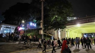 Warga berjalan melewati terowongan jalur pedestrian yang dihiasi lampu warna-warni di Jalan Kendal, dekat Stasiun Sudirman, kawasan Dukuh Atas, Jakarta Pusat, Selasa, 26 Maret 2019.
