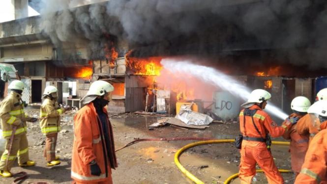 Petugas pemadam kebakaran berusaha memadamkan api.