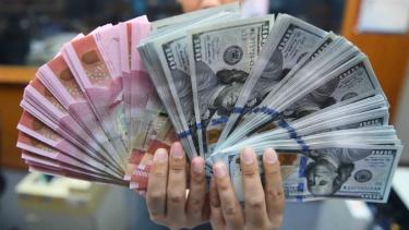 Pekerja menunjukkan uang Rupiah dan Dolar Amerika Serikat di sebuah tempat penukaran uang di Jakarta