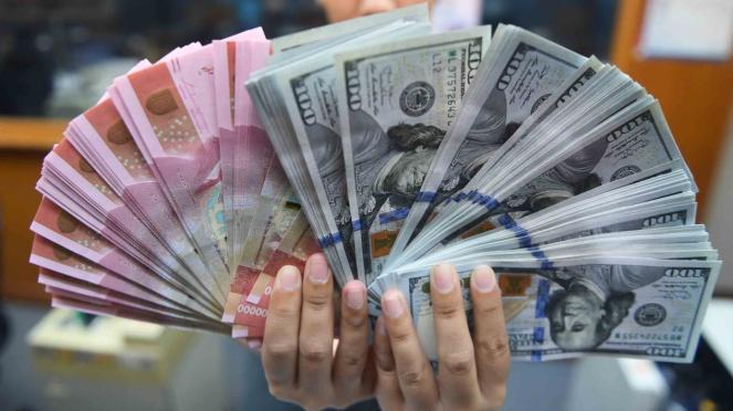 Pekerja menunjukkan uang Rupiah dan Dolar Amerika Serikat di sebuah tempat penukaran uang di Jakarta.