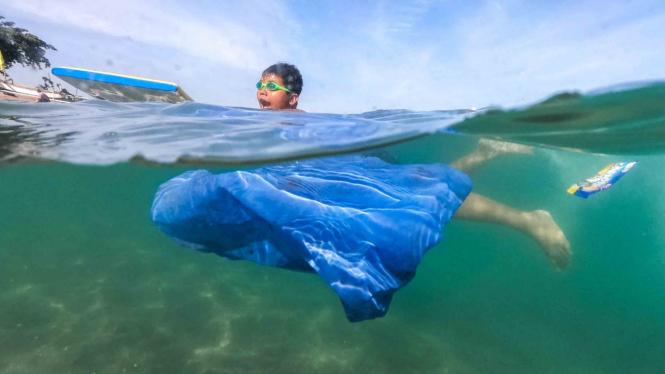Seorang anak berenang di dekat sampah plastik yang hanyut terbawa arus di pantai wisata Senggigi, Lombok Barat, NTB