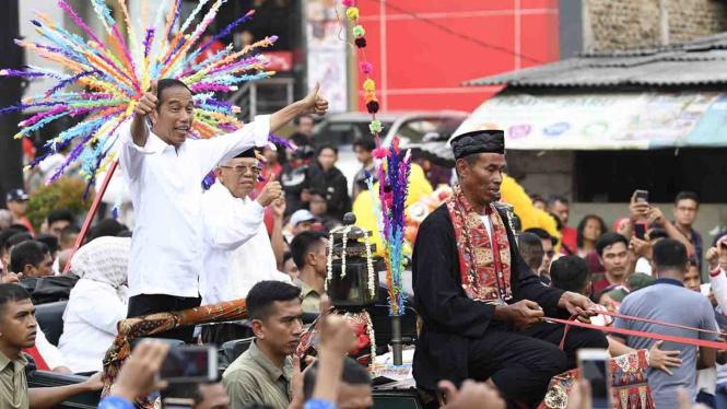 Calon Presiden dan Calon Wakil Presiden nomor urut 01 Joko Widodo (kiri) dan Maruf Amin (kedua kiri) menyapa masyarakat Tangerang saat Karnaval Indonesia Satu di Banten, Minggu, 7 April 2019.