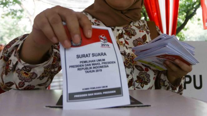 Warga memasukan contoh surat suara ke dalam kotak suara usai dicoblos saat simulasi Pemilu serentak 2019 di Jakarta