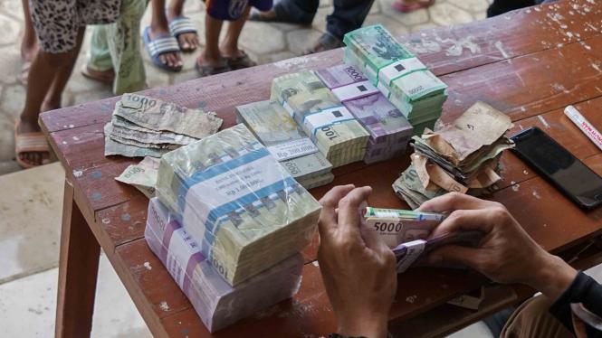 Petugas menghitung uang saat penukaran uang yang digelar oleh Tim Penukaran Uang Keliling Bank Indonesia, di Desa Klaces, Kampung Laut, Cilacap, Jateng, 10 April 2019.