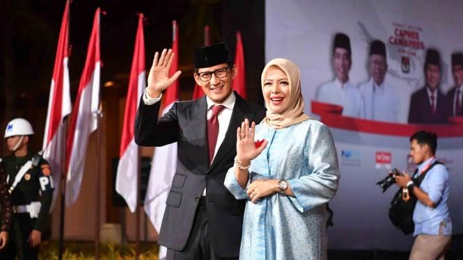Cawapres nomor urut 02 Sandiaga Salahudin Uno bersama istri Nur Asia menyapa para wartawan setibanya di lokasi debat keiima Pilpres 2019, di Hotel Sultan, Jakarta, Sabtu, 13 April 2019.