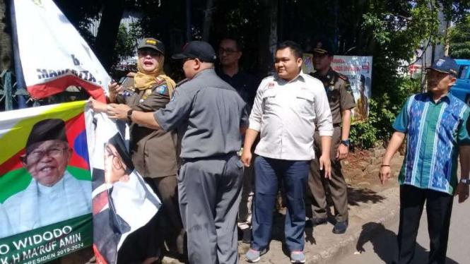 Petugas gabungan di Depok bersihkan alat peraga kampanye.