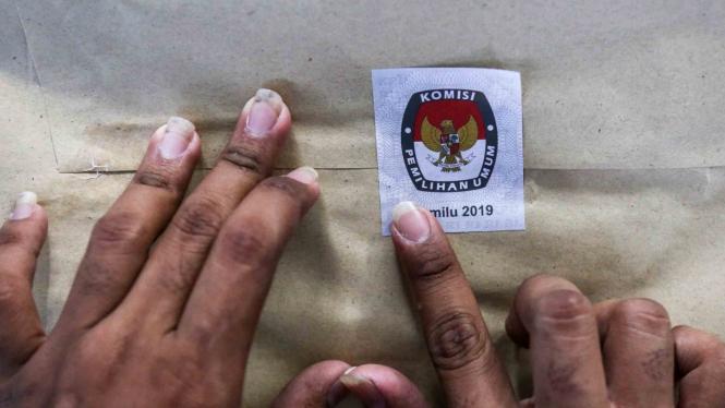 Petugas Kelompok Panitia Pemungutan Suara (KPPS) menyegel amplop yang berisi surat suara sebelum didistribusikan ke kelurahan di gudang logistik KPU Jakarta Pusat, GOR Kemayoran, Jakarta