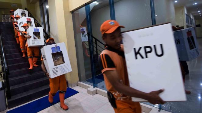 Petugas mengangkut logistik Pemilu ke dalam mobil saat akan didistribusikan ke kelurahan di gudang logistik KPU Jakarta Pusat, GOR Tanah Abang, Jakarta