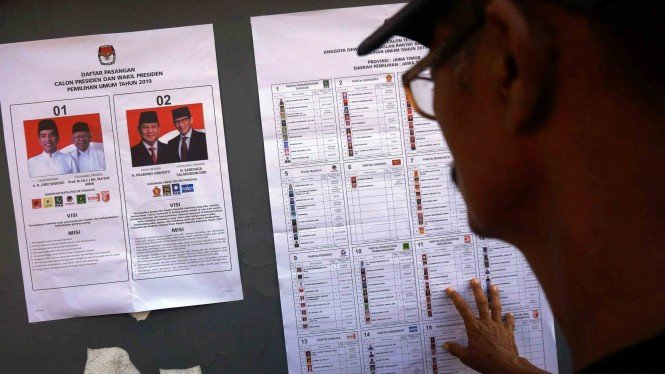 Pemilih melihat spesimen alat peraga surat suara pilpres dan pilleg sebelum menggunakan hak suaranya dalam Pemilu di TPS 11 Desa Ringinpitu, Tulungagung, Jawa Timur
