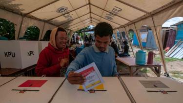 Seorang warga korban bencana memasukkan surat suara ke kotak suara usai menyalurkan hak suaranya di tenda pengusian saat pemungutan suara Pemilu 2019, di TPS 01 Kelurahan Petobo , Palu, Sulawesi Tengah