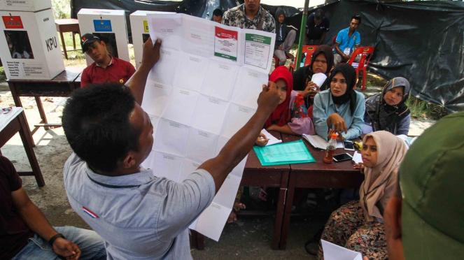 Anggota Kelompok Penyelenggara Pemungutan Suara (KPPS) menunjukkan surat suara kepada para saksi saat dilakukan perhitungan lanjutan di TPS bersebelahan dengan Pos Lanal Pusong di Desa Pusong Baru, Lhokseumawe, Aceh