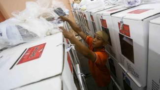 Petugas Kelompok Panitia Pemungutan Suara (KPPS) menyusun kotak suara yang berisi surat suara hasil Pemilu Srentak 2019 sebelum dilakukan rekapitulasi surat suara di GOR Mangga Dua Selatan, Sawah Besar, Jakarta Pusat