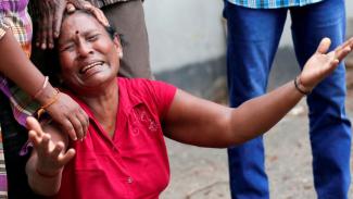 Seorang anggota keluarga tak kuasa menahan tangis ketika menunggu di luar ruang jenazah di kantor polisi di Kolombo, Minggu (21/04). - Reuters