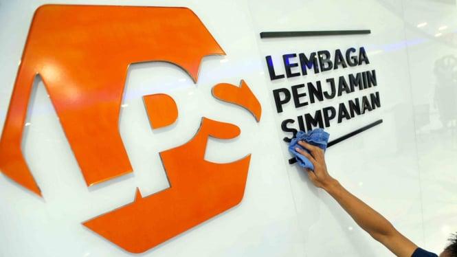 Karyawan membersihkan logo baru Lembaga Penjamin Simpanan (LPS) di Jakarta