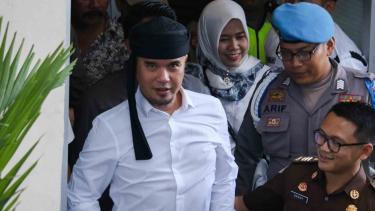 Ahmad Dhani Prasetyo (kiri) saat berjalan menuju mobil tahanan usai mengikuti sidang di Pengadilan Negeri Surabaya, Jawa Timur.
