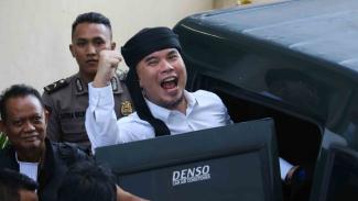 Terdakwa kasus dugaan pencemaran nama baik Ahmad Dhani Prasetyo (kanan) masuk ke mobil tahanan usai mengikuti sidang tuntutan di Pengadilan Negeri Surabaya, Jawa Timur