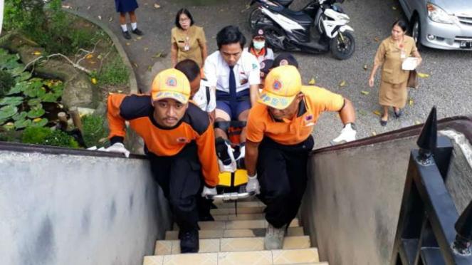Aparat BPBD Kabupaten Jembrana, Bali, menggotong seorang siswa SMP untuk mengiku