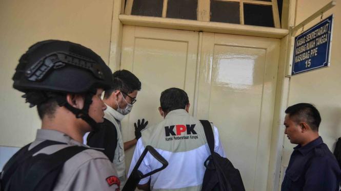 Petugas Komisi Pemberantasan Korupsi (KPK) memasuki ruangan untuk melakukan penggeledahan.